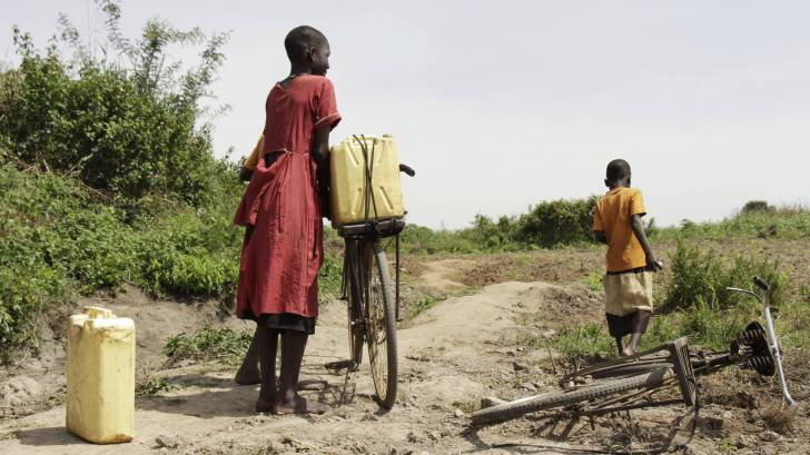 ugandan mom and son riding bikes to get fresh water