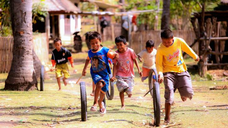 young children playing in the street,