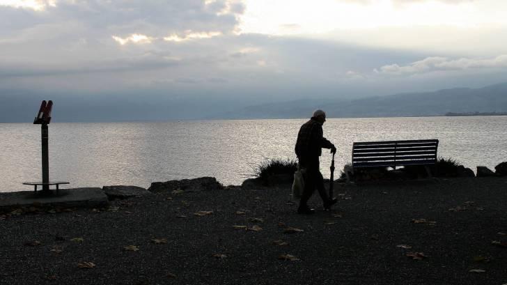 older man walking arounf the lake