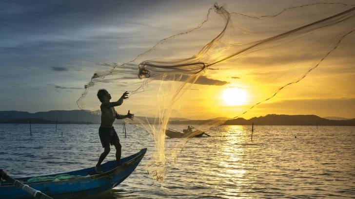 Fishermen casting nets in the sunset
