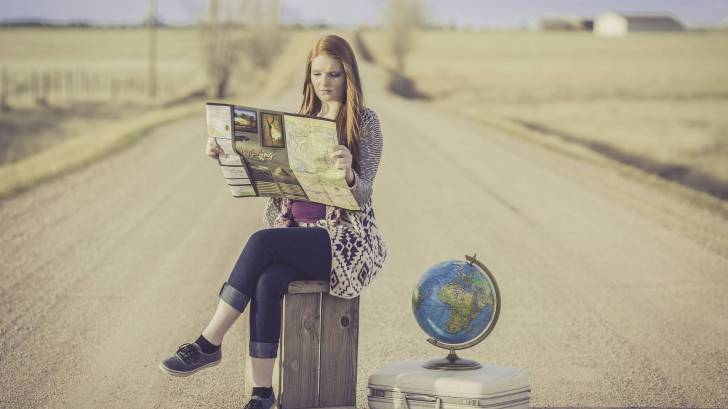 girl on road with globe looking at a map