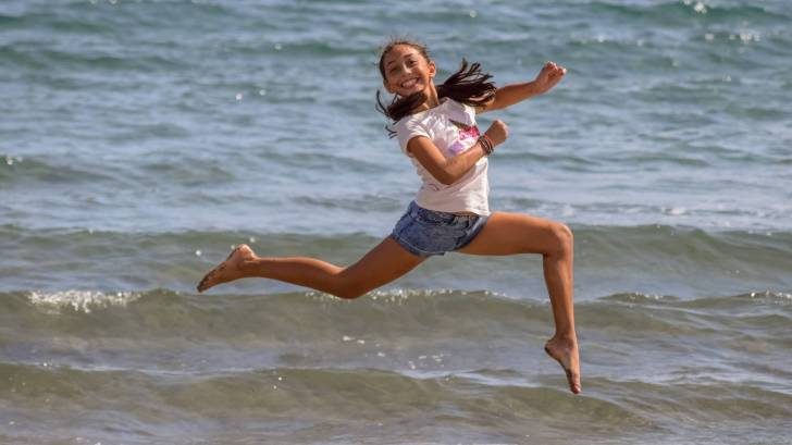 teen girl jumping for joy on a beach