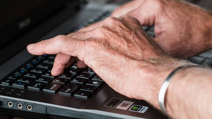 older hands with arthritis typing on a keyboard