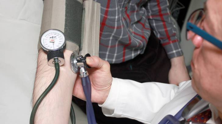 doctor taking blood pressure, counseling patient
