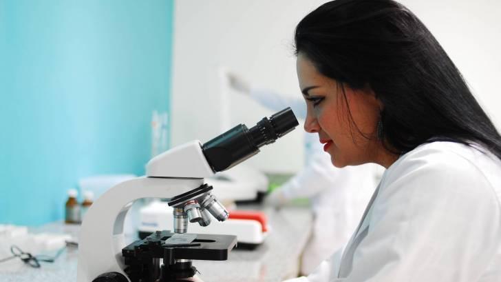 researcher looking thru a microscope