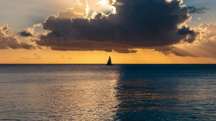 atlantic ocean sunset, yellow with sail boat in the back ground