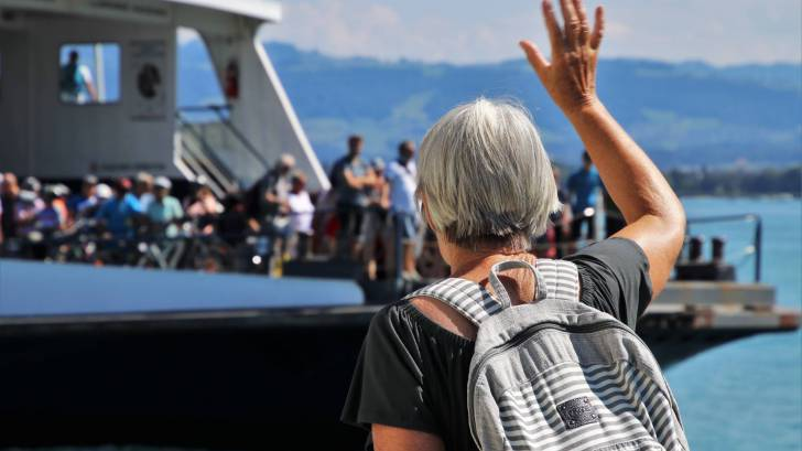 older woman waving to a ferry boat full of people