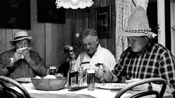 3 older men enjoying a meal with each other