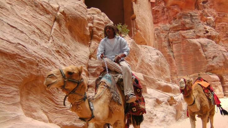 man riding a camel and pulling another behind him