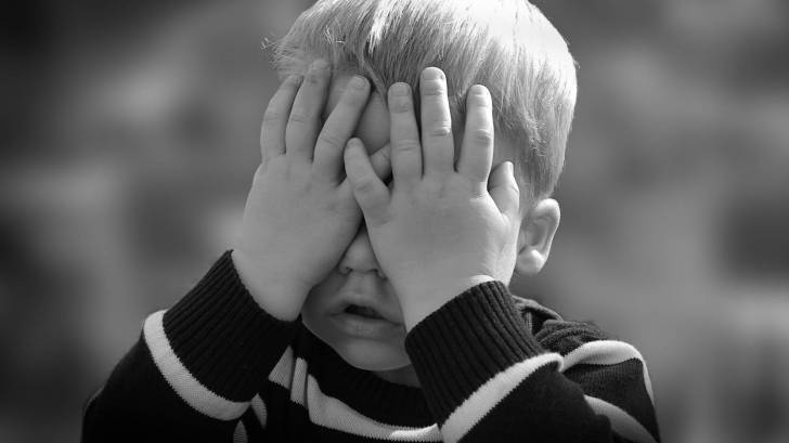 young boy covering his eyes