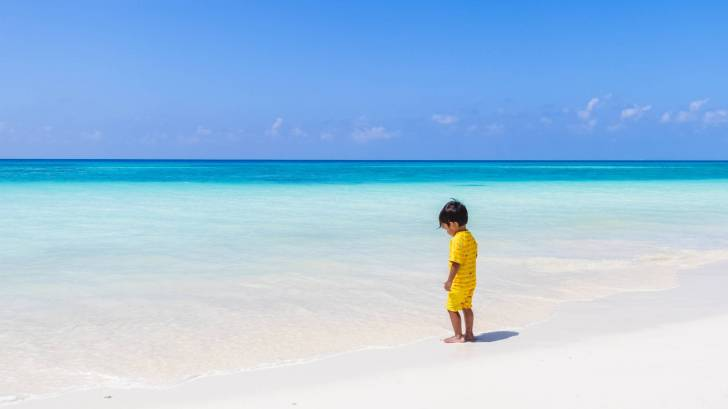 little boy on beach in yellow clothes