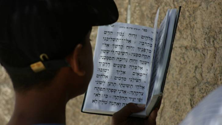 young boy reading prayers