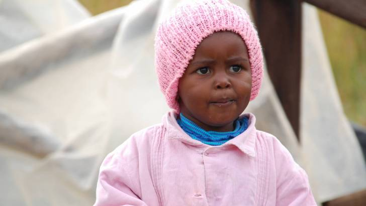 young african girl with pink coat and hat