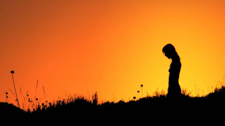 silhouette of lady with sun setting