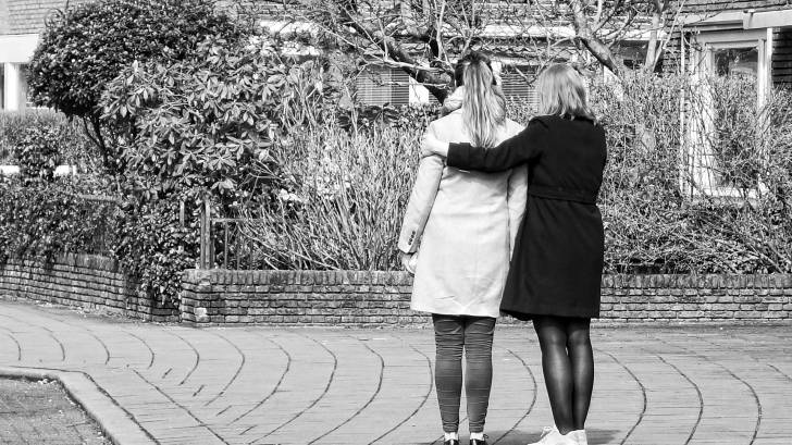 2 women holding arm in arm