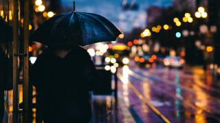 adult with umbrella in a city alone