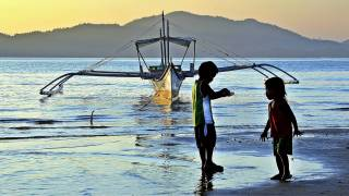 filipino children playing on the beach fishing
