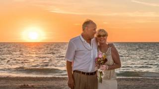 older couple on beach for wedding happy