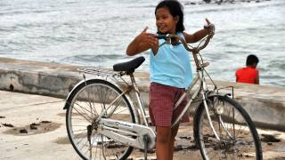 young filipino girl on a bike near the beach