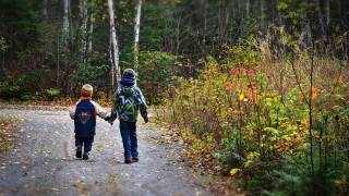 two young children walking along a road holding hands