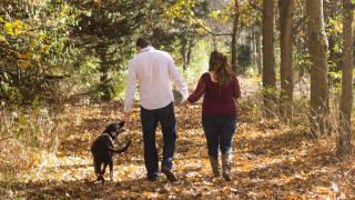 couple with dog hiking in the woods