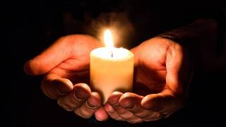hands holding a candle in pray