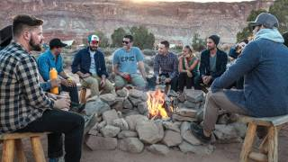 men sitting around an outdoor fire pit