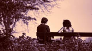 couple sitting on a park bench at dusk